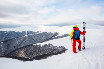 Fototapete - A skier is standing on the slope, watching the mountain scenery