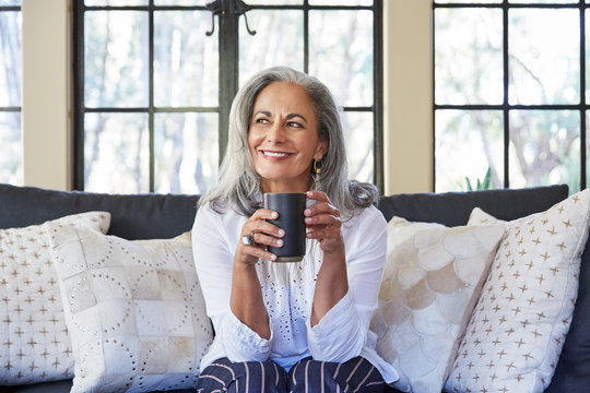 Mature woman with grey hair relaxing and drinking tea in her living room