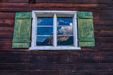 Spiegelung in einem Fenster Berge Holzhaus