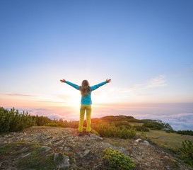 Woman expressing her inner joy in majestic landscape during sunset