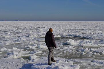 Man is standing on the ice floating at sea
