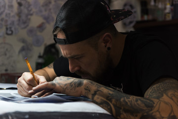 Tattooist drawing in salon
