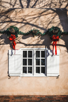 decorative holiday Christmas wreaths hanging above a window on an adobe building