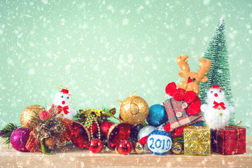 Christmas background. Christmas tree and ornaments lie on a wooden table snowy weather. Space for text. It's snowing. Merry Christmas. New Year's background. Toned image.