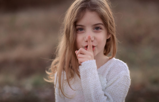 Cute little child with finger on lips making a silent gesture. Shh concept, be quiet