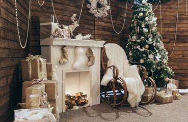 Christmas photo zone, decor. Cozy Christmas decorations. Christmas tree, fireplace, many gifts, rocking chair, lights. Cozy holiday photo. New Year's photo zone