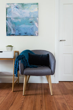 grey tub chair with rug and wall art