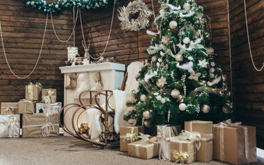 Cozy Christmas photo. Christmas decorations: rocking chair, Christmas tree, fireplace with socks, gifts on the background of a wooden wall Photo Zone. New year photo zone with fireplace and fir tree.