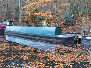a scenic view of narrow boats in a canal surrounded by golden fallen autumn leaves with reflections on the water and forest trees in hebden bridge west yorkshire