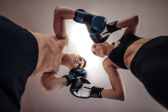 Portrait of male and female kick boxers standing against each other with boxing gloves in ring. Low angle view of man and woman at kick boxing fighting position.