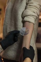 Tattooist putting transfer on hand