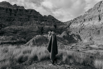 Black and White Lifestyle portrait of young adult male wearing tribal blanket in high desert unique landscape area of Oregon