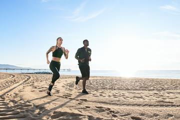Sportive couple running on the beach.