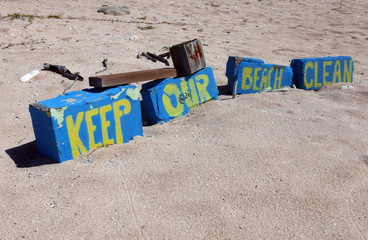 Sign Keep our Beach clean in yellow letters stenciled on blue bricks