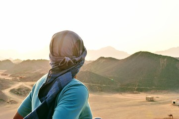 Man wearing traditional egyptian scarf watching sunset from the mountains