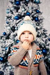 Christmas theme and children. Little Caucasian boy child in a warm hat and sweater posing, eating sweetness, dirty face. Christmas morning. New Year's holidays