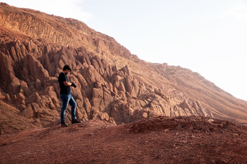 Man with a camera on top of rocks