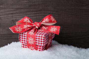 Christmas gift box on snow over wooden background