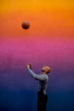 Side view of man playing with basketball