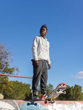 Skateboarder standing in park