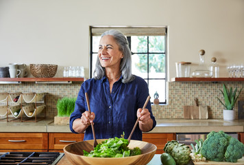 Portrait of mature woman preparing a healthy salad in the kitchen at home laughing