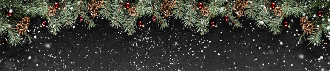 Christmas Fir branches with pine cones on dark black background. Xmas and Happy New Year card, bokeh, sparking, glowing. Flat lay, top view, wide composition