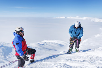 Two Professional Climbers making trekking on snowy slope.