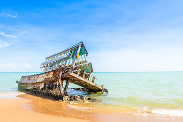 The wreckage of the fishing boat is beached  with blue sea and the blue sky as background.location Satheep Thailand