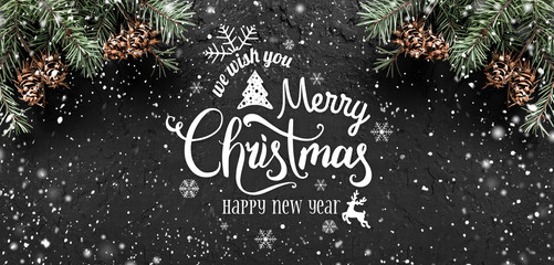 Christmas and New Year Typographical on dark holiday background with frame of Fir branches, pine cones, snowflakes. Xmas and Happy New Year theme, snow. Flat lay, top view