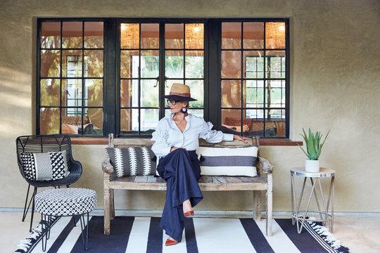 Stylish woman sitting on porch