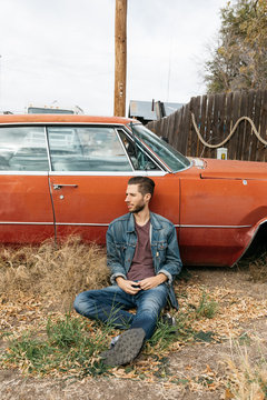 Young adult male in denim sits in front of broken down vintage car in rural town