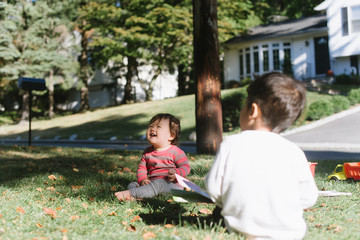 Baby and toddler playing in front yard