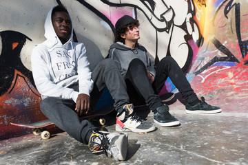 Casual skateboarders at graffiti wall