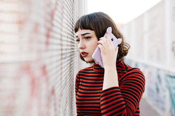 Woman speaking on phone near graffiti wall