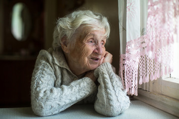 Elderly lady looks out of the window.