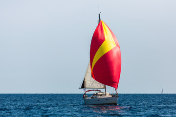 Sailing yacht with colorful bright gennaker in the regatta at Aegean sea, Greece.