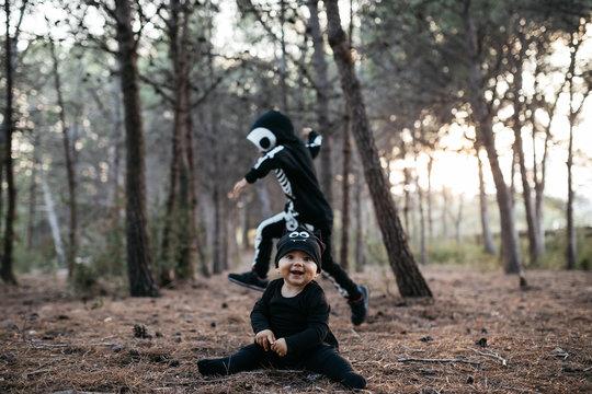 Cute baby in black bat costume against running skeleton kid in f