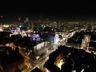 Aerial night time photo taken above the Leeds City Center at Christmas Time showing the Leeds Town Hall and buildings and roads around West Yorkshire.