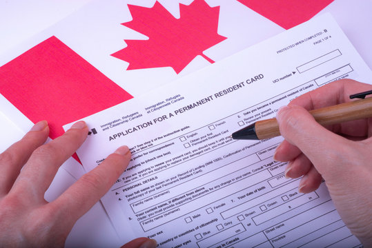 Filling Application (female hands and wood pen) form for Canadian Citizenship - Adults. Immigration, Refugees and Citizenship Canada on Canadian flag surface.