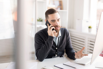 Portrait of handsome bearded businessman speaking by phone while working at desk in modern office, copy space