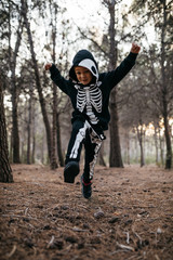 Boy in halloween costume running with his arm widened in forest.