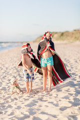 Children and dog with towels at the beach
