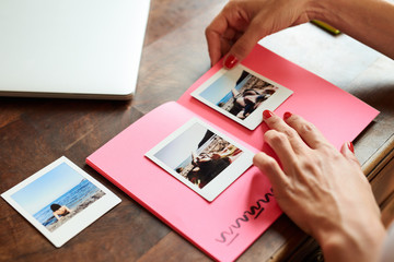 Woman making album with polaroid photos of girl on the beach.