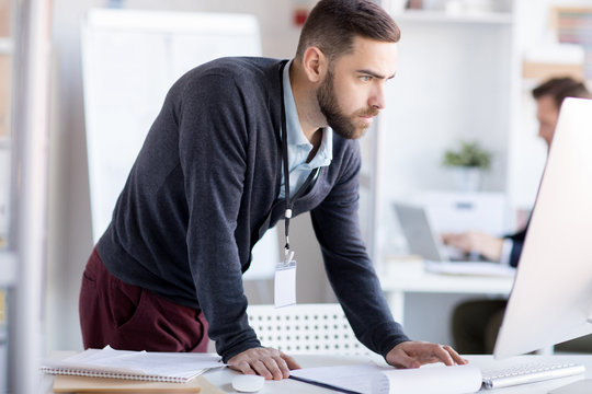 Side view portrait of bearded office worker using computer standing at desk, copy space