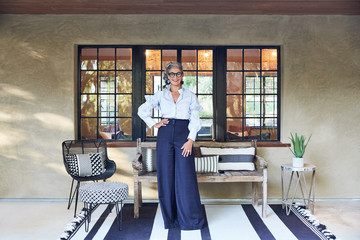 Portrait of beautiful and stylish mature woman interior designer with grey hair standing on front porch