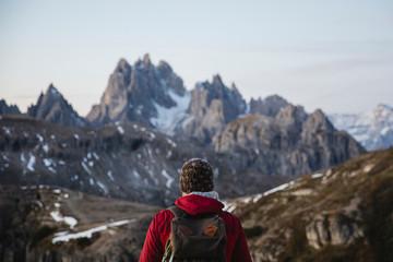 Hiker observing the rocky landscape of Dolomites