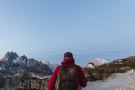 Hiker observing the landscape of Dolomites at sunrise