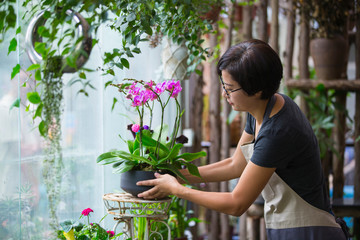 Asian female florist working in the flower shop
