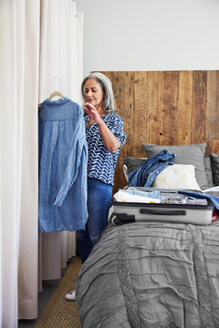 Mature woman packing a suitcase in her bedroom