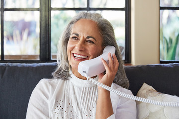 Mature woman with grey hair talking on landline phone in living room